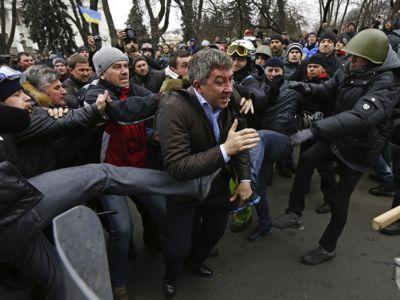 Des manifestants antigouvernementaux agressent Vitaly Grushevsky, député du Parti des régions, devant le parlement, à Kiev, le 22 février 2014.
