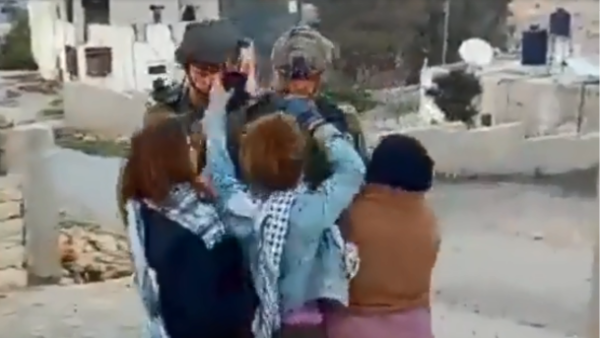 Ahed Tamimi, center, and her cousin Nour Tamimi, left, and a Palestinian woman pushing and hitting Israeli soldiers in a screen grab from a video that has gone viral, December 15, 2017.