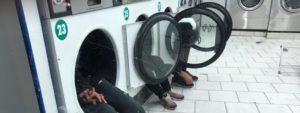 De jeunes hommes assis dans les machines d'une laverie du quartier de la Goutte-d'Or, dans le 18e arrondissement de Paris, le 20 décembre 2017 (infernale75 FRANCEINFO)