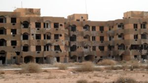 A once-inhabitated apartment block, ridden with bullet holes, stands abandoned in Tawergha on February 21, 2013. © 2013 Reuters
