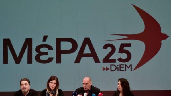 Yanis Varoufakis assis devant une représentation en néon rouge du logo de son parti, MeRA25, sur la scène d